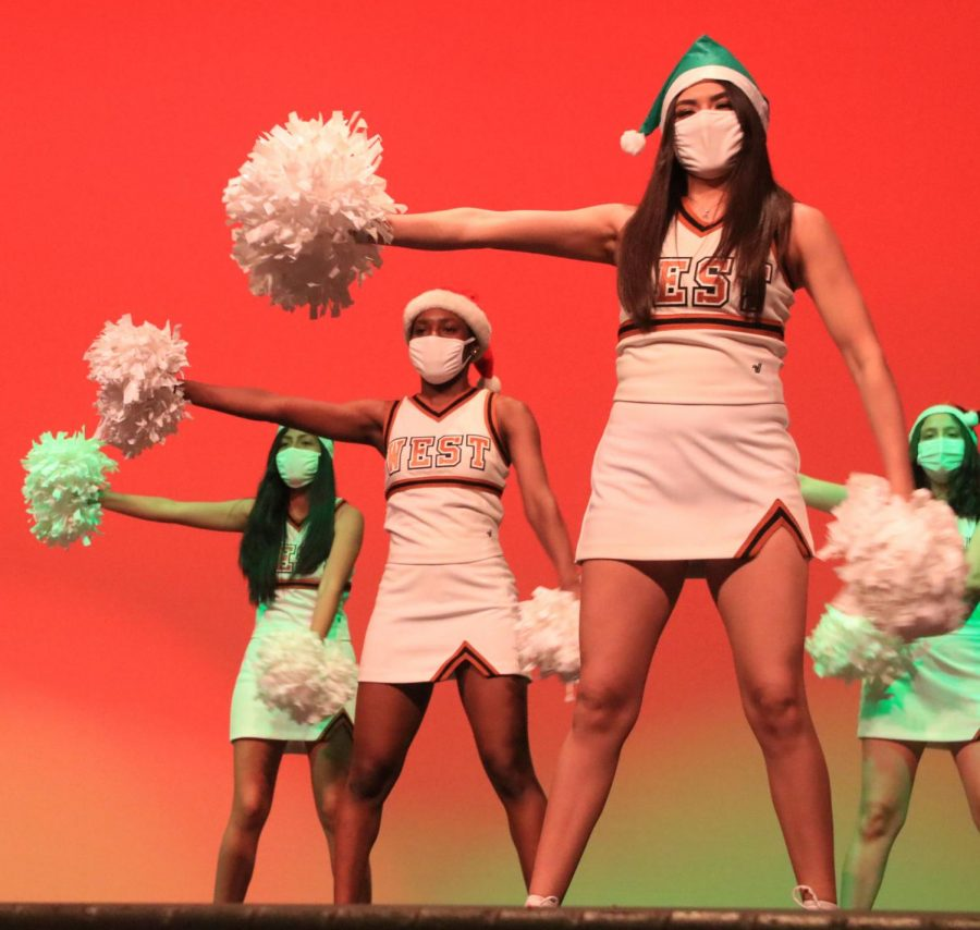 Cheerleaders perform for faculty as apart of the artmas show. They were but one group that made the day special